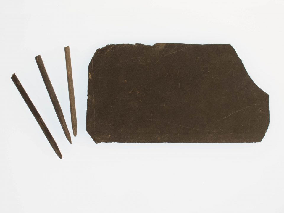 Three pencils approximately three inches long next to a rectangular slate approximately three inches by 7 inches.
